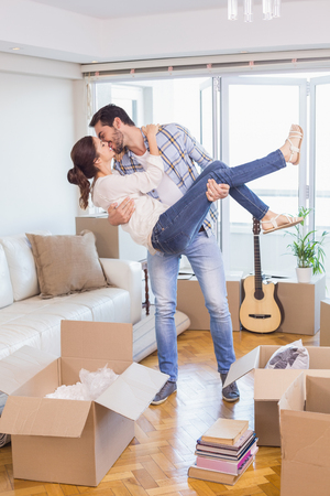 moving box: Cute couple unpacking cardboard boxes in their new home