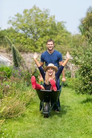 man pushing: Man pushing his girlfriend in a wheelbarrow at home in the garden Stock Photo