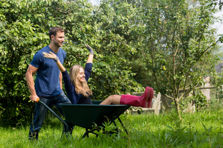 Man pushing his girlfriend in a wheelbarrow at home in the garden photo