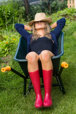 Pretty blonde napping in wheelbarrow at home in the garden photo