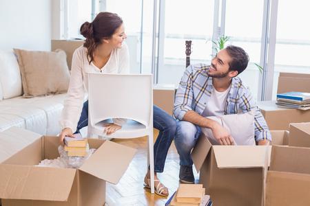 pareja en casa: Linda pareja desempaquetar cajas de cartón en su nuevo hogar Foto de archivo