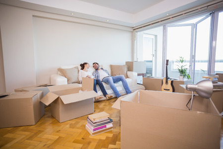 first move: Cute couple taking a break from unpacking in their new home Stock Photo