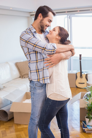 moving box: Cute couple hugging and smiling in their new home Stock Photo