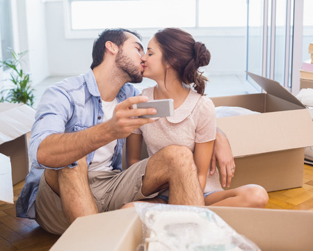 Cute couple taking a selfie in their new home photo