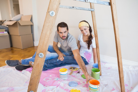 Cute couple about to paint living room in their new home photo