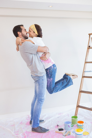 redecorating: Cute couple hugging while redecorating in their new home