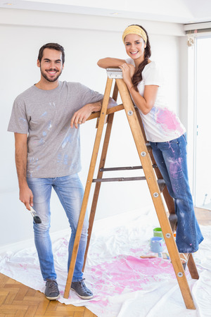 redecorating: Cute couple redecorating living room in their new home Stock Photo