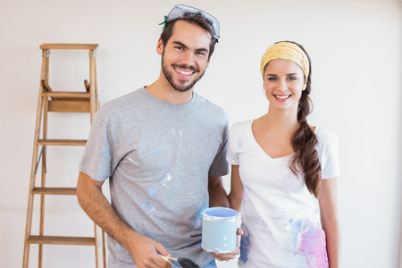 Cute couple redecorating living room in their new home photo