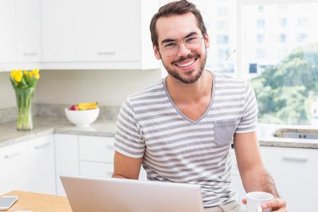 hombres jovenes: Hombre joven que usa la computadora portátil mientras que el café en casa en la cocina Foto de archivo