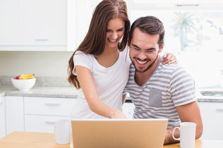 Young couple smiling and using laptop at home in the kitchen photo