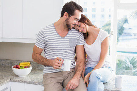 Young couple having coffee together at home in the kitchen Stock Photo