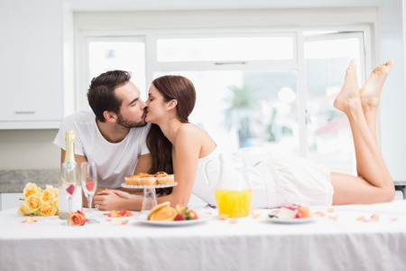 parejas romanticas: Pareja joven con un romántico desayuno en su casa en la cocina