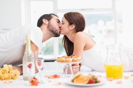desayuno romantico: Pareja joven con un rom�ntico desayuno en su casa en la cocina