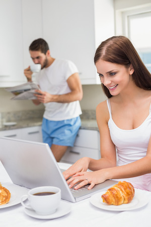 Young woman using laptop at breakfast at home in the kitchen photo