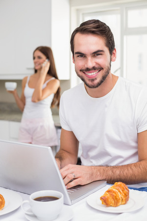 Young man using laptop at breakfast at home in the kitchen photo
