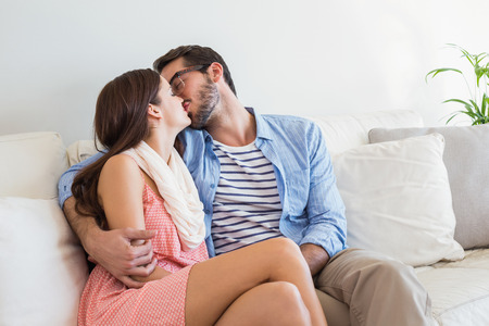 women kissing women: Young couple kissing on couch at home in the living room Stock Photo