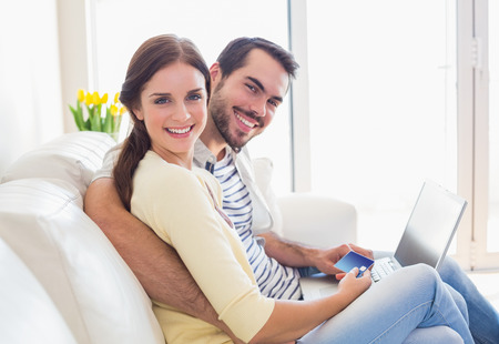 house shopping: Cute couple relaxing on couch with laptop at home in the living room