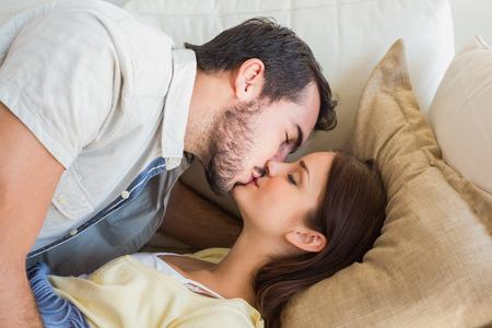 novios besandose: Linda pareja bes�ndose en el sof� en casa en la sala de estar Foto de archivo
