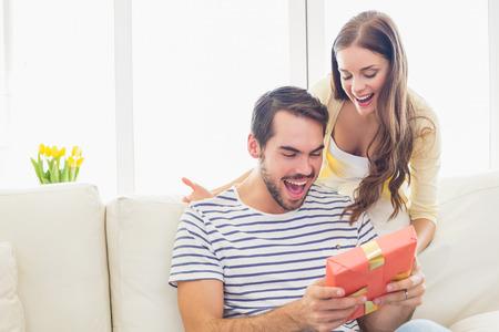 sorprendido: Mujer bonita sorprendiendo a su novio con el regalo en casa en la sala de estar Foto de archivo