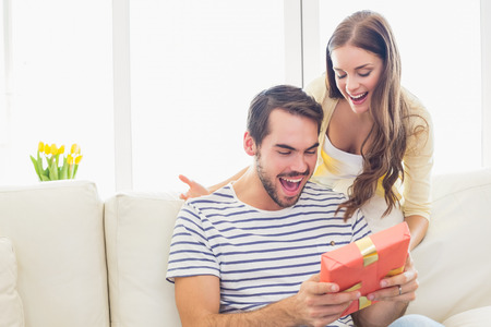 astonishment: Pretty woman surprising her boyfriend with gift at home in the living room Stock Photo