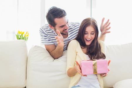 gift in celebration of a birth: Hombre asombrosamente su novia con un regalo en el sofá en casa en la sala de estar Foto de archivo