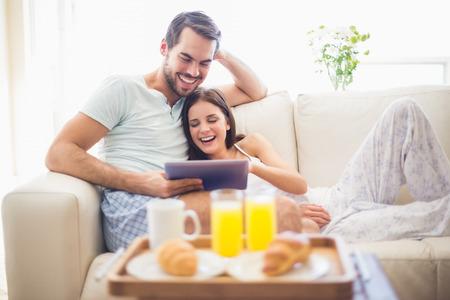 거실에서 집에서 아침 식사 태블릿과 편안한 소파에 귀여운 커플