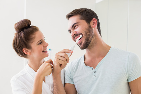 teeth cleaning: Young couple brushing their teeth at home in the bathroom