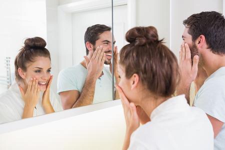 parejas felices: Pareja joven que pone en crema para la cara en su casa en el ba�o