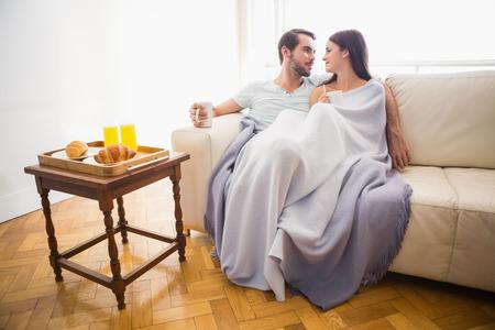 descansando: Linda pareja se relaja en el sof� bajo la manta en su casa en la sala de estar