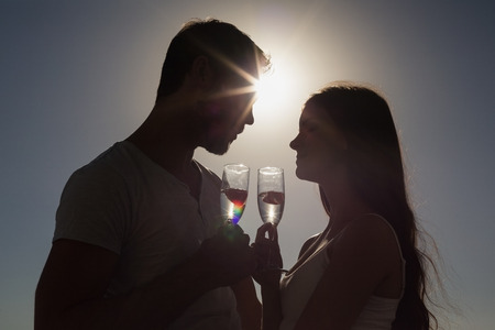 Cute couple toasting with champagne as the sun is going down photo