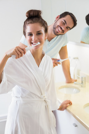 dental mirror: Young couple brushing their teeth at home in the bathroom