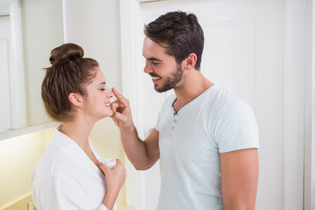 rubbing noses: Young man putting cream on girlfriends nose at home in the bathroom