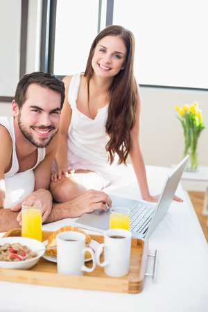Young couple having breakfast in bed at home in bedroom photo