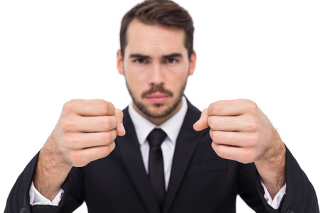 exasperated: Exasperated businessman with clenched fists on white background