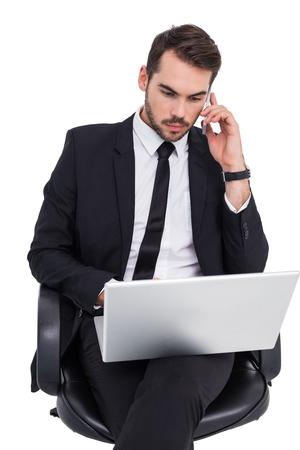 Businessman using laptop while phoning on white background