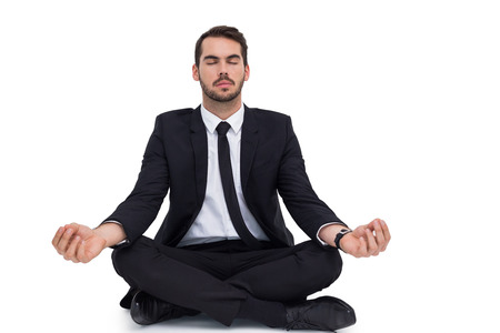 Peaceful businessman sitting in lotus pose relaxing on white background photo