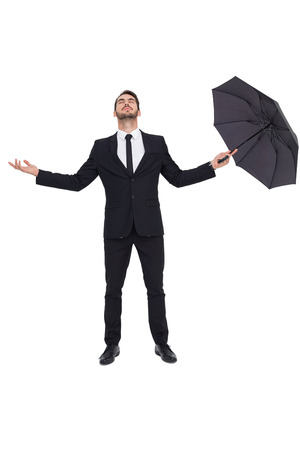 realize: Businessman with arm out holding umbrella on white background Stock Photo