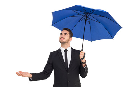 hand out: Cheerful businessman holding umbrella with hand out on white background
