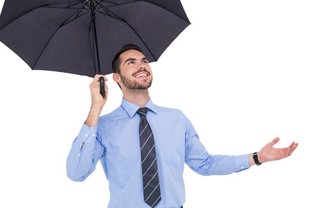 sheltering: Happy businessman sheltering with a black umbrella on white background
