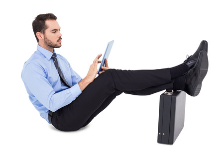 Businessman sitting using tablet with feet on his briefcase on white background photo