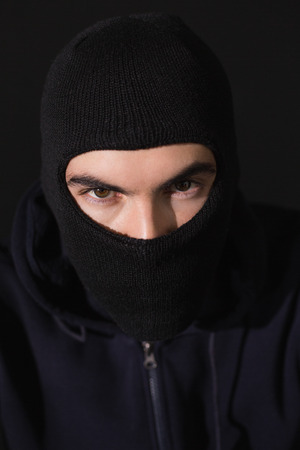 thievery: Portrait of burglar wearing a balaclava on black background