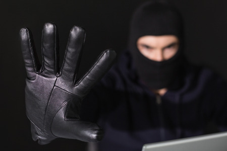 Hacker in balaclava with fingers spread out on black background photo