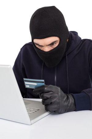 Angry hacker using laptop and credit card on white background photo