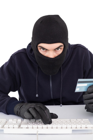 Concentrated burglar in balaclava shopping online on white background photo