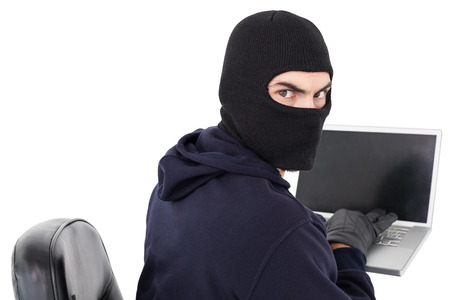 Hacker sitting and hacking laptop on white background photo