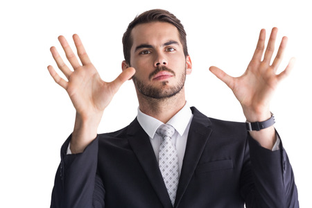 Serious businessman with finger spread out on white background photo
