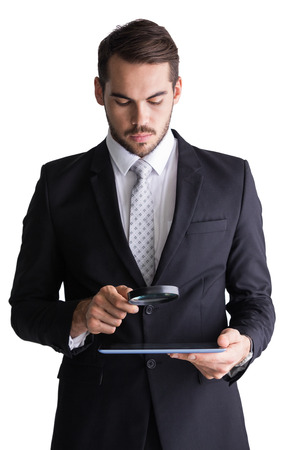 Concentrated businessman using magnifying glass on white background photo