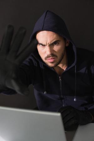 intruding: Hacker sitting at desk hacking a laptop on black background