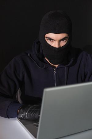 Burglar sitting hacking laptop while looking at camera on blakc background photo