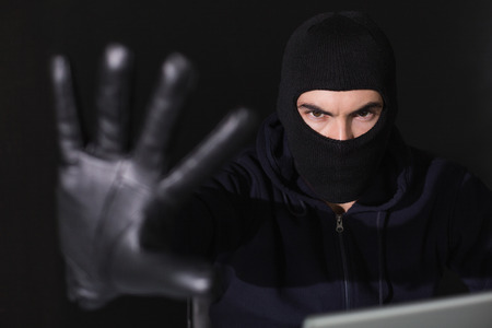 Hacker in balaclava gesturing and looking at camera on black background photo